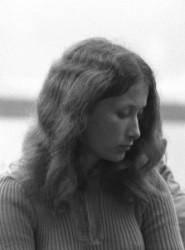 A fekete fehér képen egy fiatal lány lesütött szemmel áll, a haja vállára omlik.