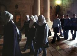 A templom előcsarnokában fejkendős arab keresztény iskolás lányok mennek Jézus sírjához. Mögöttük feljárat a Golgotához.