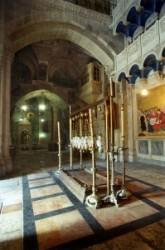 A Szentsír templom előcsarnokába beömlő napfényben a bebalzsamozás köve, felette a görög ortodox, a római katolikus, az örmény, a kopt, és Jakobita egyházak lámpása, háttér az örmény kápolna.