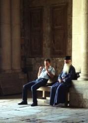 Szentsír templomban a bejárat melletti padon hosszú szakállas kék ruhás görög ortodox pap ül, izraeli rendőrrel.