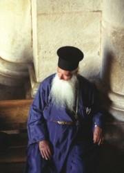 Jeruzsálem, keresztény negyed, szentsír templomban a bejárat melletti padon hosszú szakállas kék ruhában egy görög orthodox, ortodox pap. A beáradó fényben az ajtón kitekintve múlatja az időt.