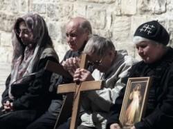 Az örmény Szent János kápolna előtt a Szentsír templom udvarán örmény zarándokok ülnek, és misét halgatnak, egyik hívő kezében kereszt, a mellette ülő hölgy kezében egy szentkép és imádkozik.