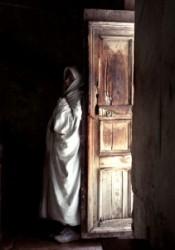 A Szentsír templom udvaráról nyíló kopt kápolna ódon bejáratánál misét hallgat egy kopt zarándok