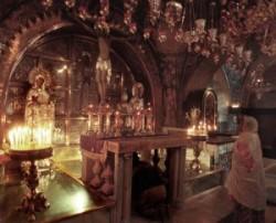 Golgota kápolnában a XII. stáció előtt, azon a helyen ahol Jézus Krisztust megfeszítették imádkozik egy zarándok. Az égő gyertyák Jézus szenvedésére emlékeztetnek.