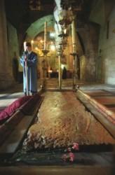 Szentsír templomban a bebalzsamozás kövénél  örmény szerzetes várja a patriarchát. A bebalzsamozás köve felett nyolc lámpa van. A megkenés kövét eltakaró márvány lap mellett virág van.