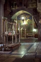 A bebalzsamozás kövét egy márványlap takarja el, fölötte lámpások vannak. Az előcsarnok kövezete legalább ezer éves. Hátérben a Három Mária kápolnában gyertya fénylik, A falon mozaik látható.