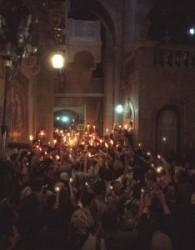 Az emberek kezében égő fáklyák, gyertyák vannak. Egymásnak adják át az örömtüzet, az örömhírt, Jézus feltámadásáról. A Szentsír templom előcsarnokát az égő fáklyát és gyertyák világítják meg.
