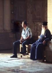 A bejárat melletti padon üll egy izraeli rendőr, és az idős szakállas görög ortodox pópa kék ruhában.