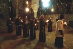 Ferences szerzetesek miséznek, kezükben gyertya, és ima könyv. a Szent Helena kápolna padlózatán az örmény holokausztról kirakott mozaik emlékezik meg.