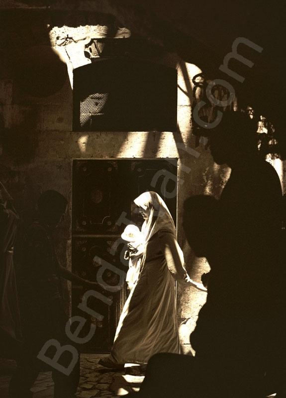 Arab nő gyerekekkel siet dolgára Jeruzsálem óvárosának arab negyedében. A sötét sikátorba beszűrődik a nyári nap sugara. A Via dolorosa, Jézus szenvedésének útja ma a legzajosabb része az arab negye