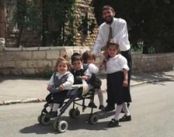 Sabbatk van. A családfő ünnepi ruhában sétál négy gyerekével Izrael fővárosában Jeruzsálem ultraortodox negyedében Mea Shearimban.