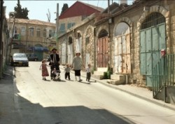 Ortodox zsidó család ünnepnapi sétája. Az apa tolja a gyerekkocsit, jobbján nagyobbacska leányka, a gyerekkocsiban a család legkisebb tagja, az anya jobb és bal kezén két apró legény vidáman lépk