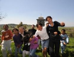 Vidám gyerekek játszanak a harangtorony előtt. Mögöttük a görög katolikus atya kedves mosollyal figyeli a gyerekeket. A völgyben Rakaca falu házai láthatók.